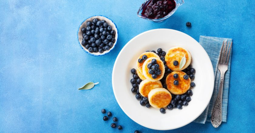 Cottage cheese pancakes or curd fritters decorated honey and blueberry in plate on blue table top view. Healthy and diet breakfast | © Juliasudnitskaya | Dreamstime Stock Photos