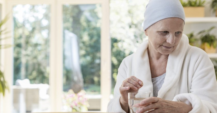 Woman suffering from ovarian cancer wearing bathrobe and headscarf taking pills at home. | © Bialasiewicz | Dreamstime Stock Photos