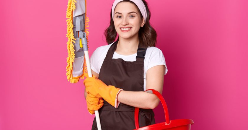 Smiling female wears brown apron and yellow rubber gloves, holds mop and red bucket. Young woman cleans house. Beautiful girl does | © Sementsovalesa | Dreamstime Stock Photos