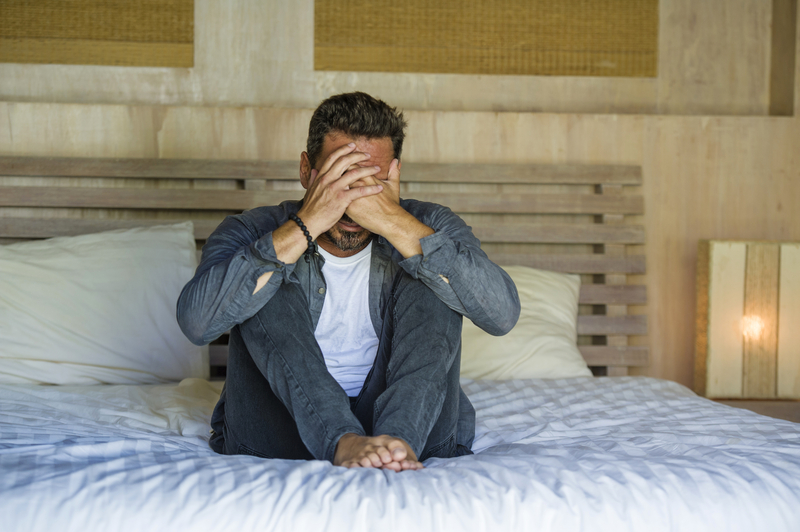Young attractive stressed and depressed man sitting on bed worried and frustrated suffering depression crisis covering face with | © Marcoscalvomesa | Dreamstime Stock Photos