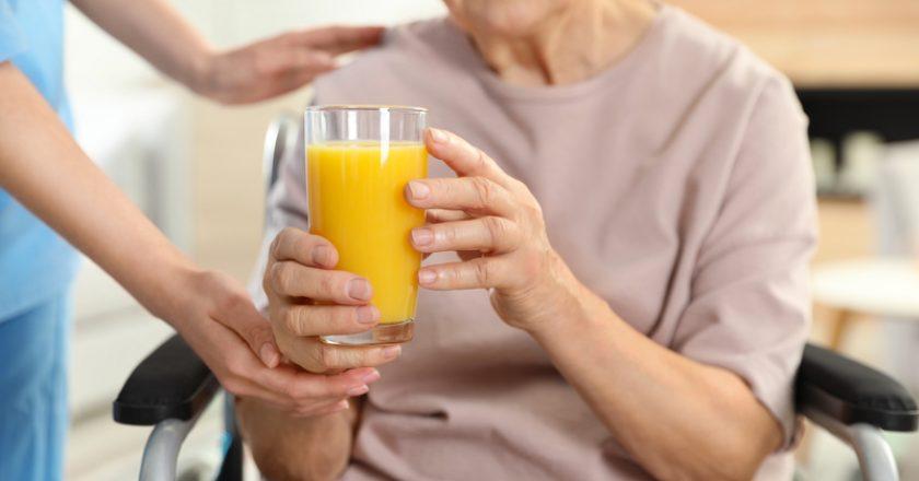 Nurse giving glass of juice to elderly woman indoors. Assisting senior people   © Chernetskaya   Dreamstime Stock Photos