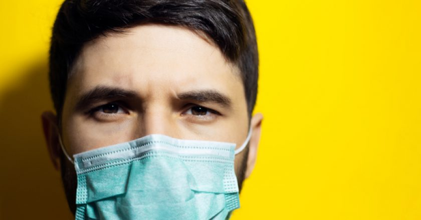 Close-up portrait of male face, wearing medical flu mask on background of yellow color with copy space. |