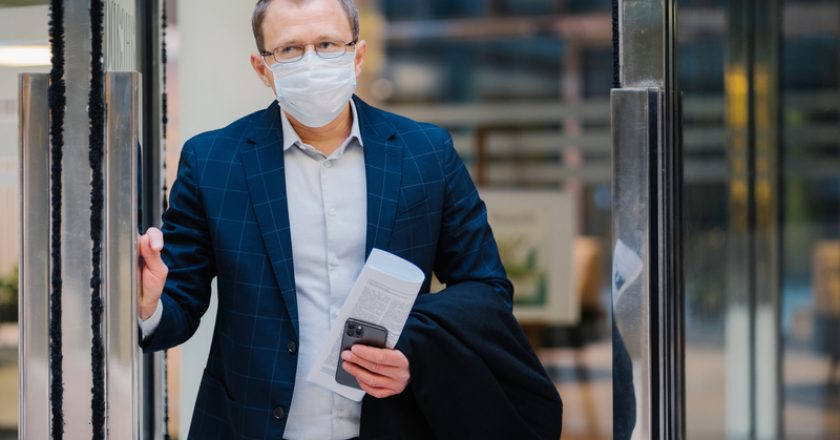 Covid-19, pandemic coronavirus concept. Office worker leaves work, wears medical face mask for infectious disease spread, dressed | © Viorelkurnosov | Dreamstime Stock Photos