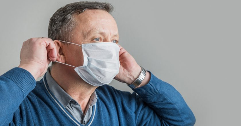 Adult man puts on surgical mask to protect against virus Covid 19. Prevention of Coronavirus |