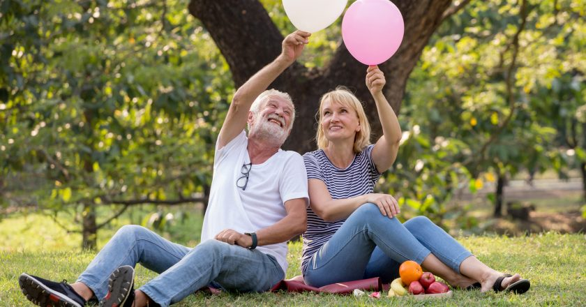 Happy senior couple relaxing in park playing balloons together . old people sitting on grass in the summer park . Elderly resting