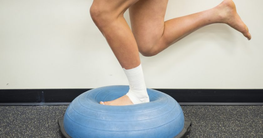 Athlete with a sprained ankle doing strengthening and balance exercises on a bosu ball | © Kbycphotography | Dreamstime Stock Photos