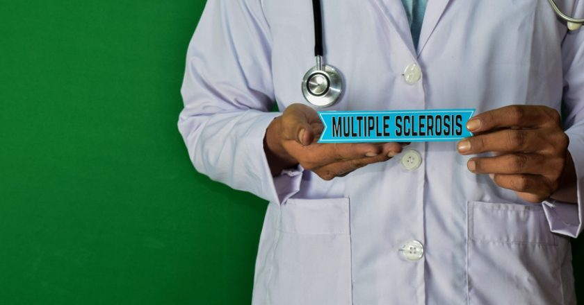 Doctor standing on Green background. Hold the Multiple Sclerosis paper text. | © Olandah23 | Dreamstime Stock Photos