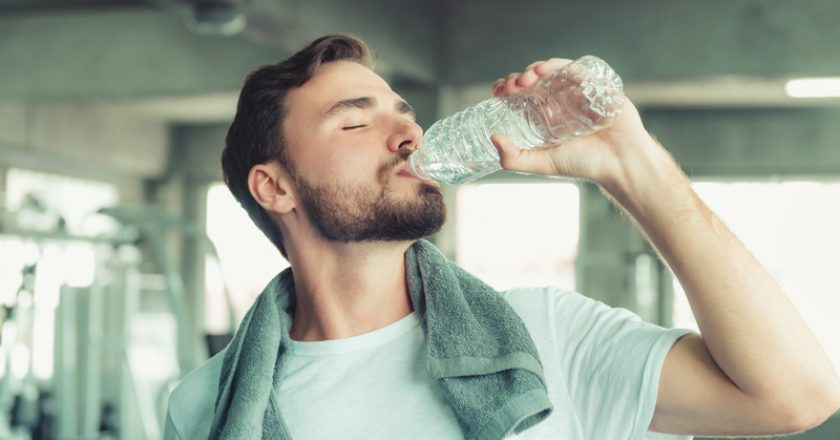 Portrait of Sport Man in Fitness Club and Drinking a Bottle of Water After Braking Exercised on Bodybuilding Equipment Background | © Khwaneigq | Dreamstime Stock Photos