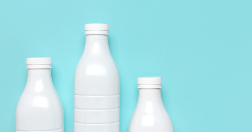 White plastic bottle containers for dairy products on blue turquoise background top view flat lay. Plastic Kefir Yogurt Milk   © Olgaarkhipenko   Dreamstime Stock Photos