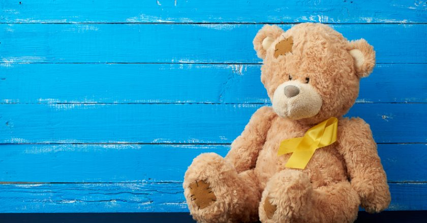 Brown teddy bear sits and a yellow silk ribbon on a blue wooden background, concept of the fight against childhood cancer | © Nndanko | Dreamstime Stock Photos