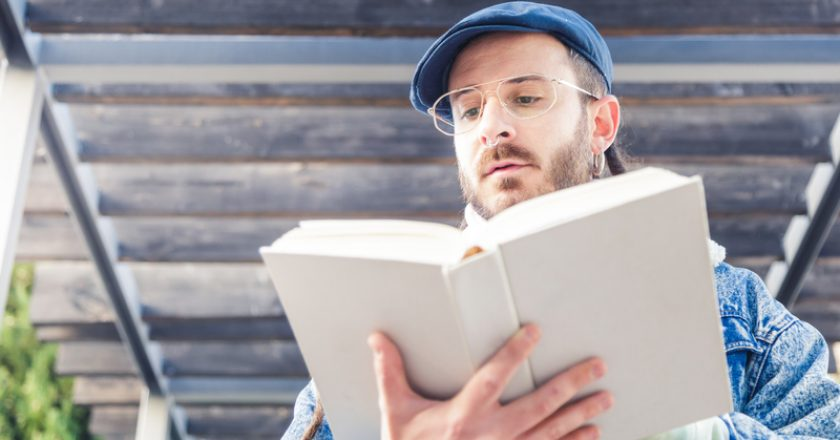 Young man wearing glasses and a cap reads a book | © Alvarotejero83 | Dreamstime Stock Photos