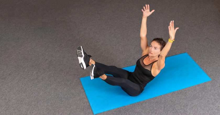 Strong and sporty fitness woman in black sportswear doing abdominal exercises and holding hands up on blue yoga mat at gym. Sport |