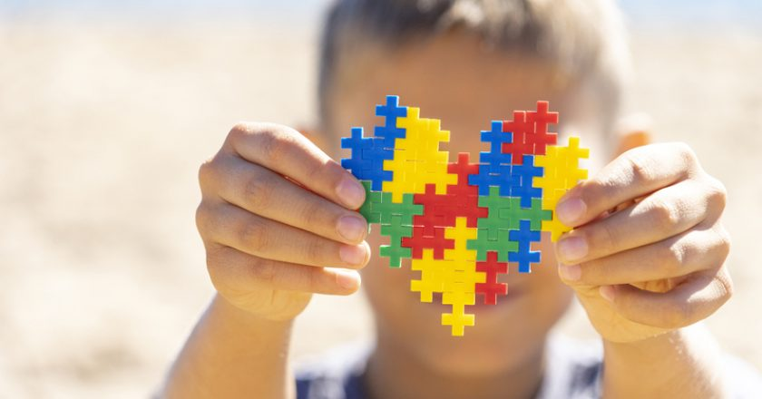 Boy holding colorful puzzle heart in front of his face. World autism awareness day concept | © Vadreams | Dreamstime Stock Photos