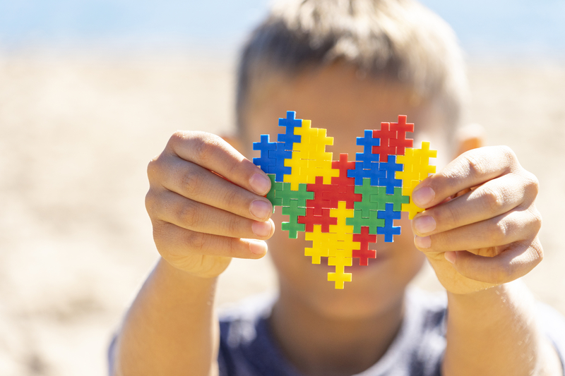 Boy holding colorful puzzle heart in front of his face. World autism awareness day concept   © Vadreams   Dreamstime Stock Photos