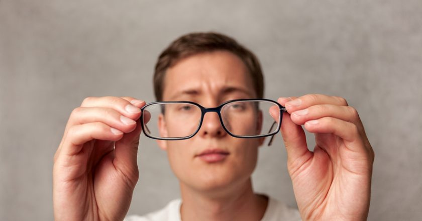The young man holds glasses with diopter lenses and looks through them, the problem of myopia, vision | © Dubovdaniilyu | Dreamstime Stock Photos