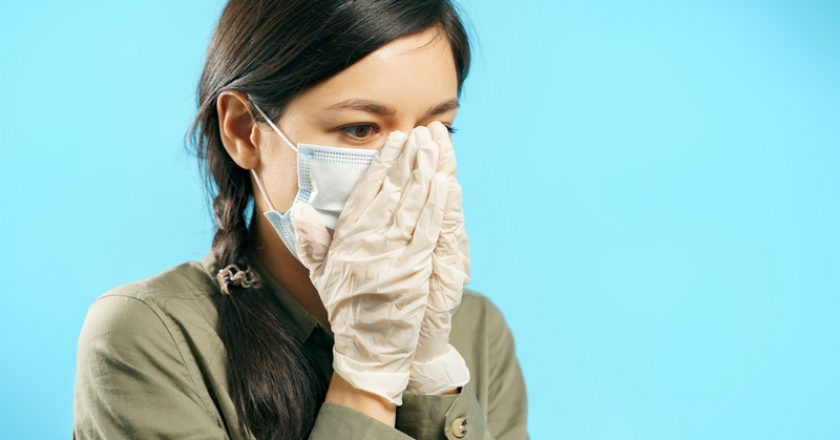Portrait of a scared woman in a surgical mask covering her face with hands in protective gloves on a blue background | © Ermilovart83 | Dreamstime Stock Photos