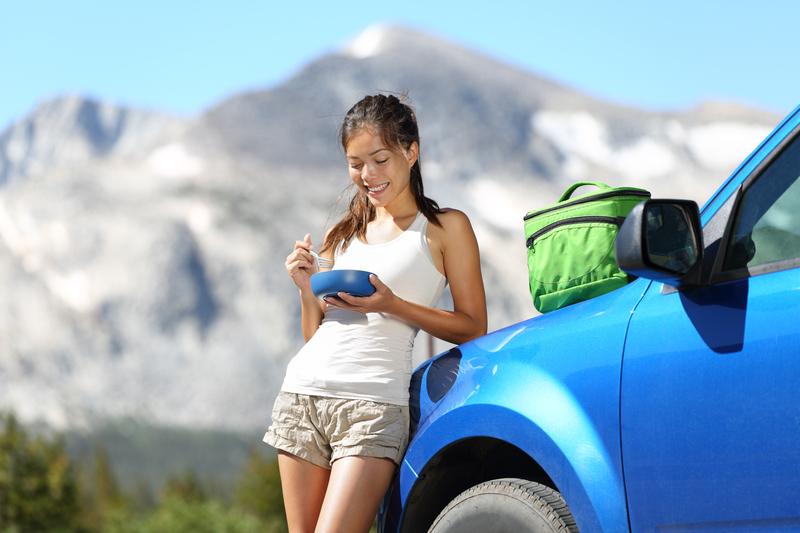 Car road trip woman eating in Yosemite Park | © Martinmark | Dreamstime Stock Photos