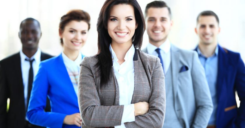 Happy young female business leader standing in front of her team | © Opolja | Dreamstime Stock Photos