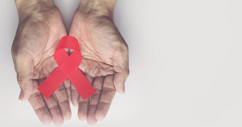Man holding red aids ribbon, HIV/AIDS and aging awareness month concept | © Zenstock | Dreamstime Stock Photos